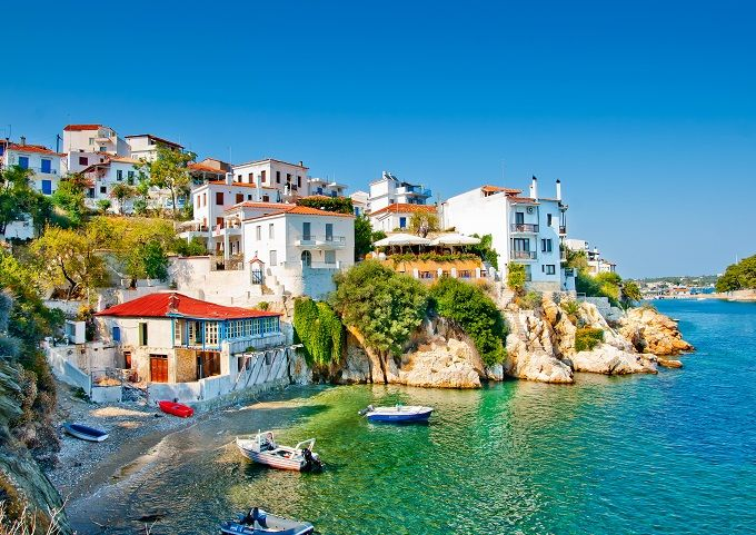 Skiathos, Greece, white buildings with red roofs in a bay, boats lined up.