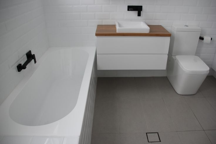 AFTER! Inner west Sydney bathroom. Bevelled white subway wall tile. Black wall mounted fixtures. Grey flecked floor tile.