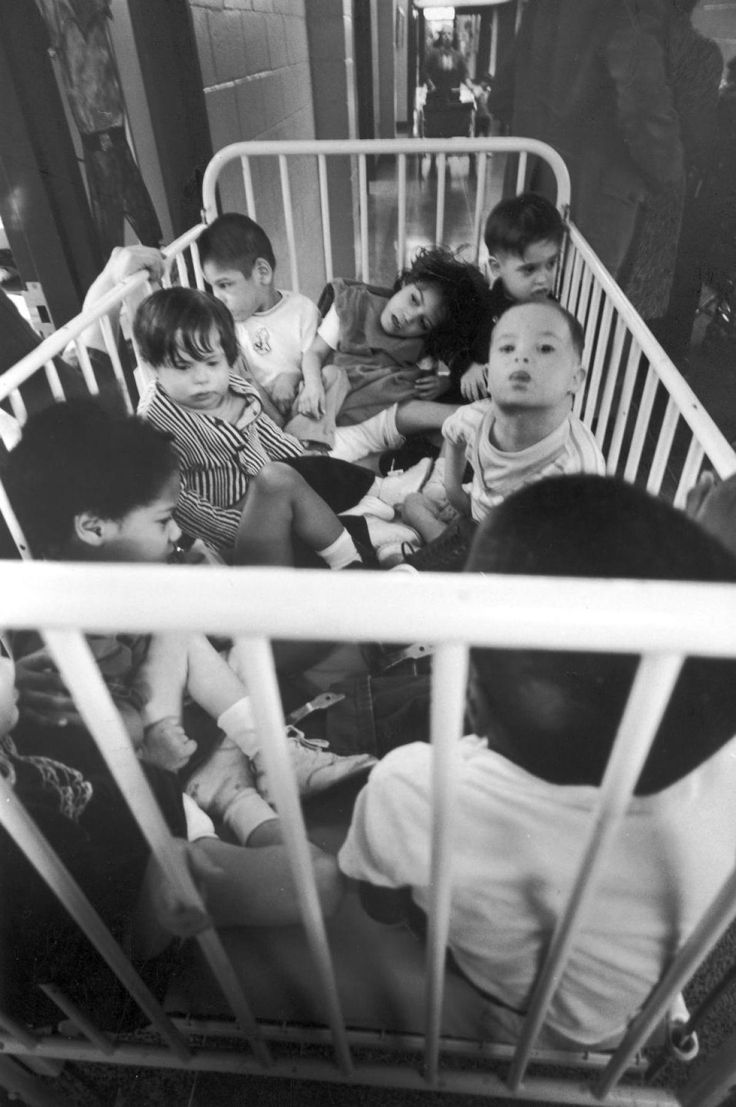 A group of eight young patients sit, crammed into a crib, prior to receiving physical therapy at Willowbrook State School, Staten Island, New York, January 1972.