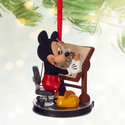 Mickey teste ses talents artistiques avec cette décoration style esquisse. Incluant l'adorable souris et des détails imitation velours, c'est un charmant complément pour tout sapin de Noël.