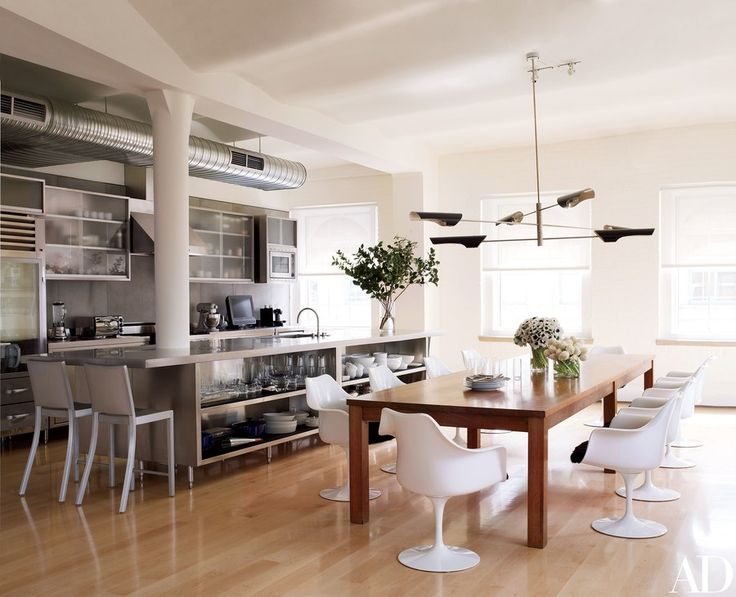 A chandelier by David Weeks for Ralph Pucci lights a set of Eero Saarinen Tulip chairs by Knoll in the kitchendining area; the Hudson counter stools are by Emeco.