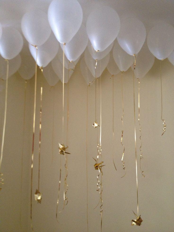 Idea de decoración para bautizo, globos transparentes (van pegados al techo!), cinta dorada y grullas hechas de origami
