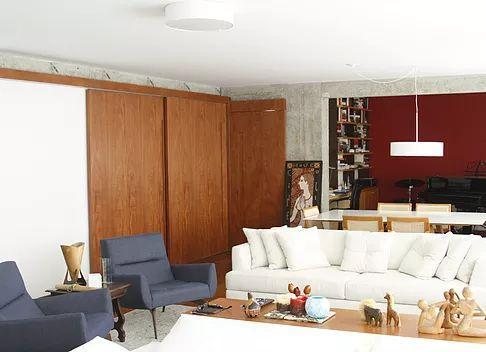 Sala de estar integrada com sala de jantar. Portas de correr de madeira da cozinha, permitem que a cozinha fique totalmente integrada com a sala ou fechada. Vigas e pilares no concreto aparente, parede vermelha, pendente sobre mesa de jantar.