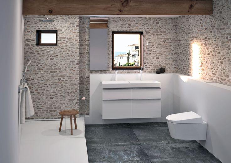 Deze rustieke badkamer geeft je een op-en-top vakantiegevoel. De sobere lichte kleuren, ruwe stenen muur en houten balken creëren een unieke mix van strak en cottage. •••