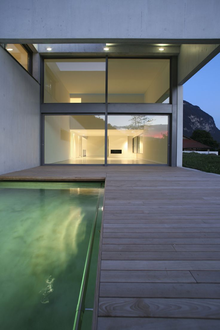 Modern flat pack home with a pool at dusk.