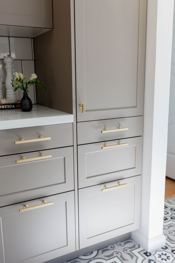 Light gray shaker cabinets w/ brass hardware for lowers cabinetry