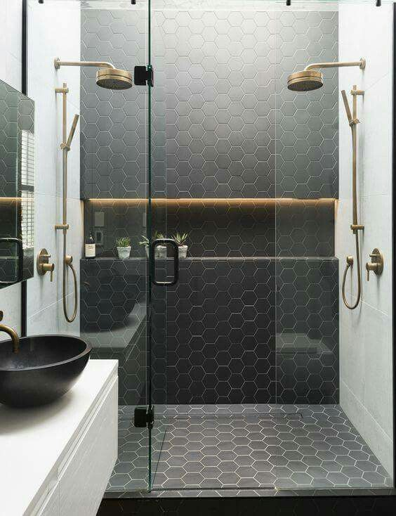 Love the gold shower fixtures and the shampoo shelf.