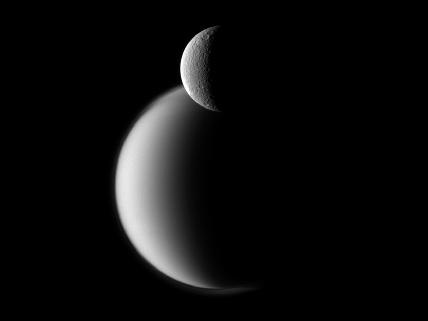 Cassini Spacecraft photo of two of Saturn's moons; crater marked Rhea in front of the much larger Titan.: Spacecraft Photo