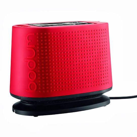 Grille-pain composé d'une structure métallique avec une base noire et coque recouverte de caoutchouc de coloris rouge. Ce modèle fait partie de la collection Bistro éditée par Bodum.