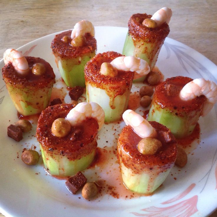 Cucumber & chamoy shots clean out the seeds I used the back of a plastic spoon then add chamoy all around and dip into the tajin the you add a lil tajin on the inside as well as a few drops of chamoy followed by adding some peanuts and chaca chacas fill up with some clamato and add the shrimp as a lil extra decor
