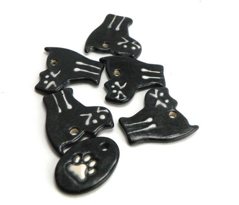 """6 stoneware pendants in cat and paw design. Each has been glazed, by hand and high fired for durability. They measure as follows: Oval Cat Paw: 1 inch by 1 3/8 inch  Black Cats: 1 3/8"""" by 1 1/2"""" (at the widest points)  Glaze colors:  Black and White"""