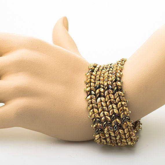 Mooie bruin en bronzen verklaring armband. Deze elegante armband is perfect om een formele slijtage, vrijetijdskleding, avondjurk of wat je wilt. Het is ook ideaal als cadeau voor de feestdagen. De Manchet armband kralen met Tsjechische SuperDuo twee holes kralen in platte herringbone stitch.  De sluiting is door de gesp van een vak in goud vergulde messing. Measurments: Lengte van de armband is 7,3 inch (18,5 cm) met inbegrip van de gesp. Breedte van de armband is 1,18 inch (3 cm).  Meer…