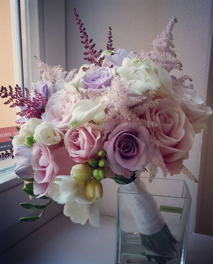 Wedding bouquet made with roses, freesia and astilbe