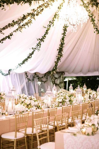 Glamorous white tented wedding reception with gold and greenery decor; Featured Photographer: Nancy Neil