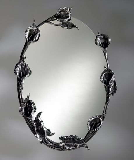 """""""Calla Lily Wall Mirror""""  Metal Mirror  Created by Bill Masterpool  One of a Kind  Hand-forged steel calla lilies gracefully frame an oval wall mirror. Flowers and stems are forged with a variety of welding processes, then tapered and textured with hand tools. The steel is wire-wheeled to a soft finish, and protected with clear lacquer. Each is unique and will vary."""