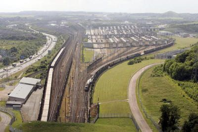 Trains enter the Channel Tunnel in Folkestone, England. The Channel Tunnel is a 50 km long rail tunnel beneath the English Channel at the Straits of Dover, connecting Folkestone, Kent in England to Coquelles near Calais in northern France.