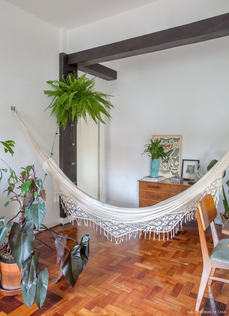 Muitas plantas e rede de balanço na sala de estar desse apê em São Paulo.