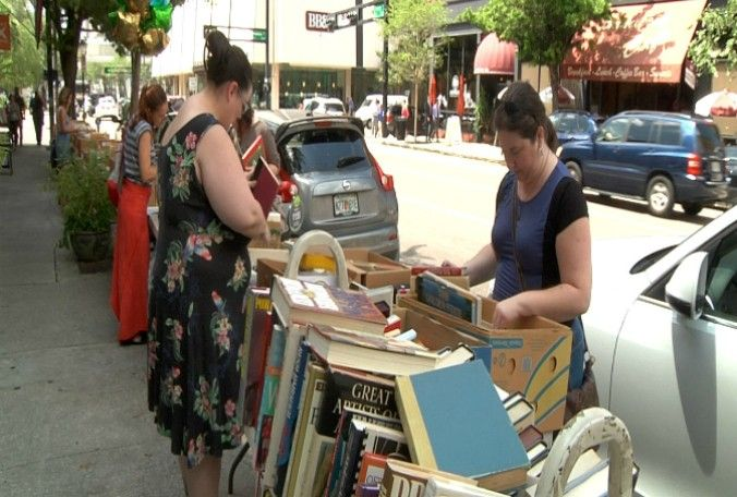 What can't fit inside goes outside. The shop has set up tables along the sidewalk piled with boxes of books. (Sara Belsole, Bay News 9)
