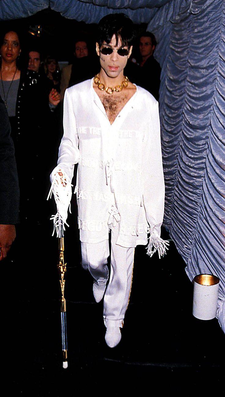 Prince, le dandy funk Round House, Londres, 3 septembre 1991.  En chemise blanche largement déboutonnée aux manches à franges et pantalon assorti, Prince chemine à l'aide d'une canne vers la scène tel un messie de la mode.