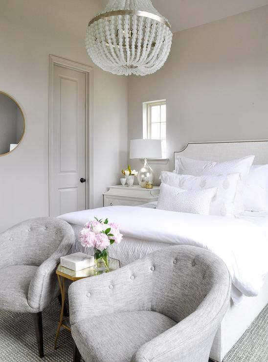 "Elegant gray and white bedroom features gray tufted accent chairs placed in front of a white French bed on either side of a Bertram 16"" Mirrored Side Table lit by a Currey & Co Chanteuse Chandelier."
