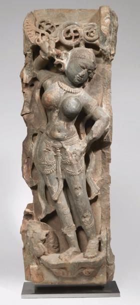 INDE, Rajasthan - Xe siècle   Stèle en marbre gris, apsara debout en léger tribhanga, parée de riches bijoux, la main gauche levée et tenant une branche de fleurs et surmontée de trois fleurs rondes, la main gauche posée sur sa hanche. (Accidents et restaurations). Dim. 81 x 27 x 16 cm