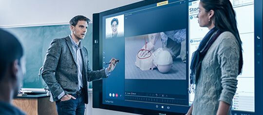 Man and woman talking in front of Microsoft Surface Hub with several apps on screen