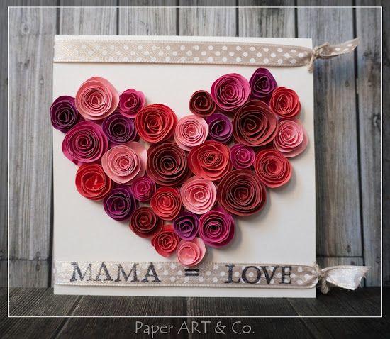 Une très jolie carte pour la fête des mères. Ce sont des roses en forme du cœur. On a besoin du papier cartonné blanc, du papier en différentes couleurs comme rouge et rose et du bolduc.
