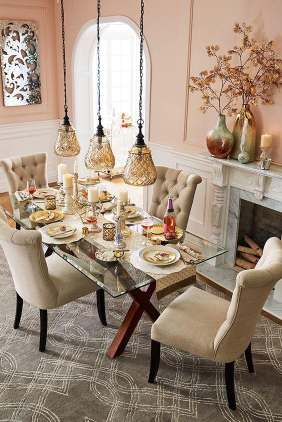Criss cross stained wooden legs with a glass top and cozy neutral upholstered chairs for a cozy dining space