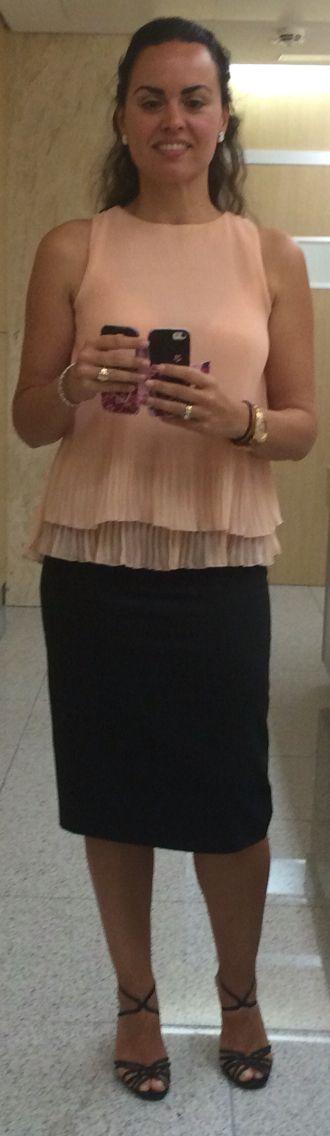 Blusa plisada de gasa rosa palo, falda lápiz negra con raya diplomática y sandalias de tiras negras con tacón dorado