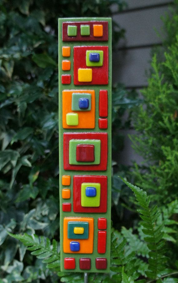 "Bright colorful contemporary garden art stake adds color to your planters all year long. The greens & reds in a modern geometric motif glass art stake makes a unique accent. All pieces are hand cut, then fused in the kiln to keep their dimensionality. They're glued to the stainless steel stake w/waterproof flexible glue, then a layer of 100% silicone caulk. Approx. 2.25x10.5"" (glass portion); with stake, approx. 26"" tall."