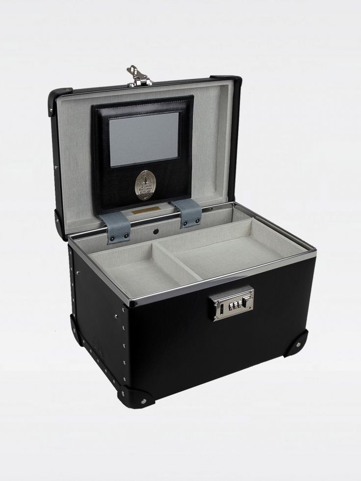 Special edition item to commemorate 100th year anniversary       Black vanity case A special material invented in Britain during the 1850's consisting of multiple layers of bounded paper Black leather (cow) trims Top and side handles Base wheels Metal studs on the leather parts Debossed logo stamp Grey canvas lining Internal mirror Combination lock to fasten at front A partitioned removable tray  Two internal straps Dimension: 32 x 22 x 20 cm Weight: 2 kg Handmade in England