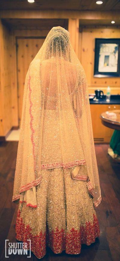 Sangeet Lehengas - Light Gold Sequinned Lehenga with Red Border | WedMeGood | Red Detailing on Gold Sequinned Lehenga with Net Dupatta as Veil #wedmegood #indianbride #indianwedding #lehenga #gold #sequinned #bridal