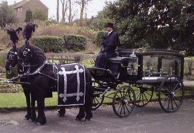 Picture of horse drawn hearse with two black horses