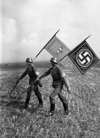 The standards of the Italian Duce and the German Fuhrer are carried to the command point during manoeuvres in honour of Mussolini. The Italian President, Benito Mussolini, was making his first state visit to Germany. September 26, 1937