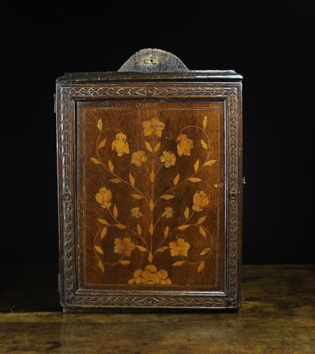 An Attractive 18th Century Inlaid Oak Spice Cupboard. The panel decorated with an inlaid flowing plant with delicate scrolling stems framed by a band of ebony and boxwood stringing, within an outer carved frame. The door on iron butterfly hinges,
