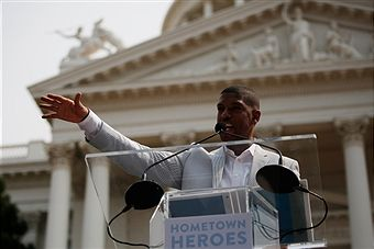 Sacramento Mayor Kevin Johnson speaks on stage during a parade honoring Alek Skarlatos, Anthony Sadler, and Spencer Stone for their August 21 actions in overpowering a gunman on a Paris-bound train on September 11, 2015 in Sacramento, California. Thousands lined the street along Capitol Mall to celebrate their hometown heroes.