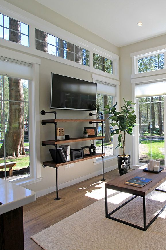 The entertainment center is surrounded by large windows, allowing for a bright living room in this tiny house.
