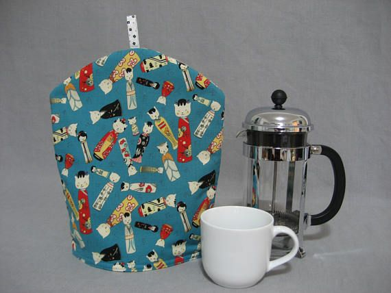 The Kitty Kokeshi in the name of this French Coffee Press Pot Cozy refers to the name of the fabric. Its a fun cotton, asian inspired cat motif, with many multi-colored happy cats. The lining is a bright cotton with a white background and small black squares and gray dots. The tab at the top of the Cozy is made of the interior cotton, and the tab is easy to grasp and remove the Cozy from the Press Pot. The Cozy is lined with quilt batting, to keep your coffee warm. The Cozy is 13 1/4 in...