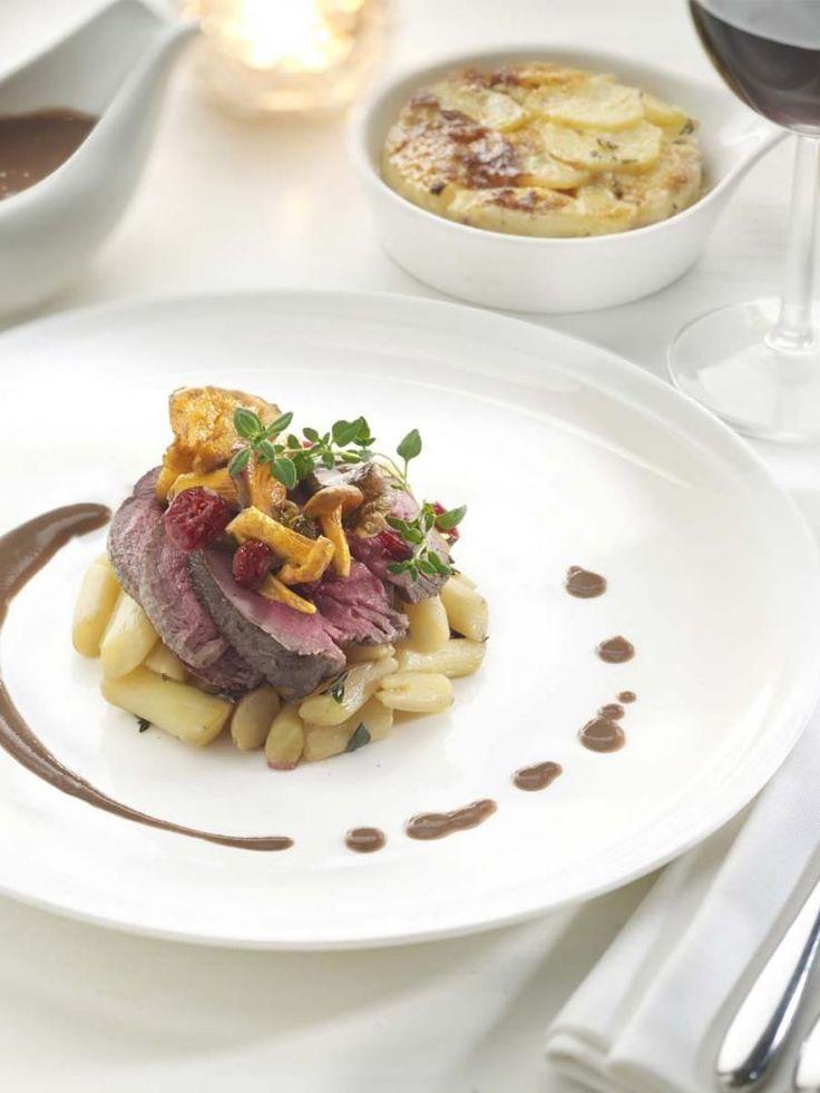 Bereiden:Maak het hertenkalf: Tip: Afhankelijk van het hertenkalfgebraad kan het handig zijn om het met touw op te binden. Kleur het hertenkalfgebraad aan in bakolie op een hevig vuur, totdat het mooi gekleurd is en voeg er nadien nog enkele klontjes boter aan toe. Plaats in de oven samen met 1 fijn gesneden sjalot, tijm, laurier en jeneverbes. Gaar op 160°C tot het geheel mooi rosé gebraden is (55-60°C kerntemperatuur). Laat even rusten na het garen. Maak de aardappelen: Snij ...