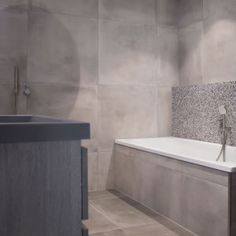 Kleine robuuste maatwerk badkamer. De vloer en muren is zijn betegeld met betonlook tegels, deze worden onderbroken door Bricks Ministeck tegels die achter het bad geplaatst zijn. Verder is de badkamer ingericht met RVS kranen, een handdouche bij het ligbad en een regendouche. Ook het eiken badmeubel, grijze wastafel en spiegel met LED-verlichting mogen niet ontbreken. De matzwarte designradiator maakt het geheel af. Ideaal voor kleine ruimtes / #design_badkamers_breda…