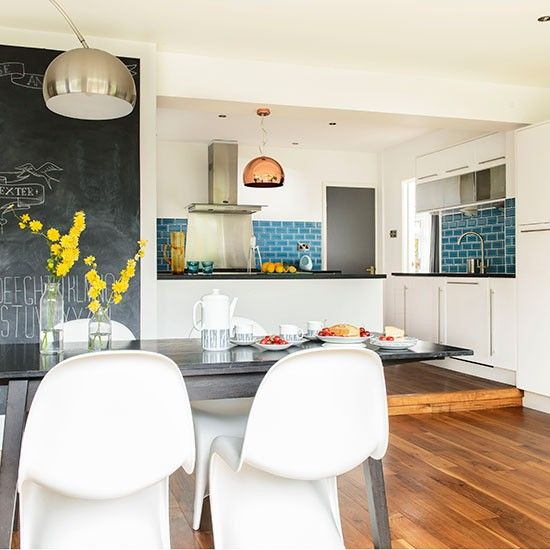 White kitchen-diner with teal tiles. I like the bright tiles against the white cupboards.