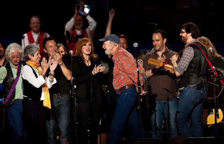 From L to R, Arlo Guthrie, Joan Baez, Bruce Springsteen, Patti Scialfa, Pete Seeger, Dave Matthews, and Tao Rodriguez celebrated onstage at Seeger's 90th birthday concert at Madison Square Garden in NYC in 2009.