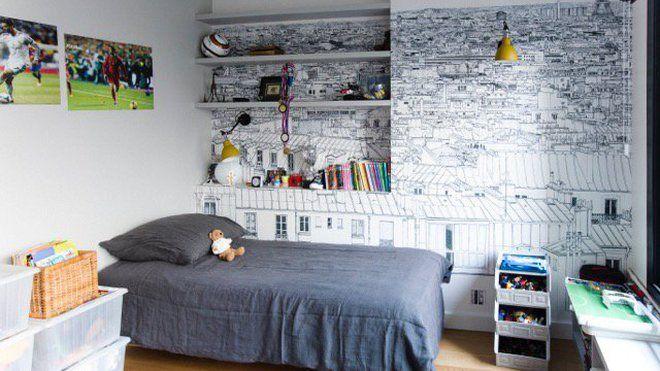 Hommage à Paris dans cette chambre d'adolescent qui offre un mur tapissé d'un papier-peint panoramique monochrome et graphique (modèle Vue de Paris Invalides Tour Eiffel, chez Ohmywall). La niche accueillant des étagères a été créée pour donner du volume à la pièce à la configuration très simple.