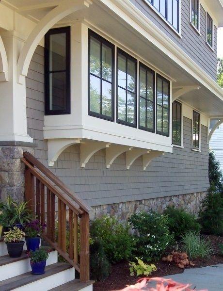 Fieldstone veneer for foundation. Black window sashes. Gray shingle siding. corbels under window boxes, eaves