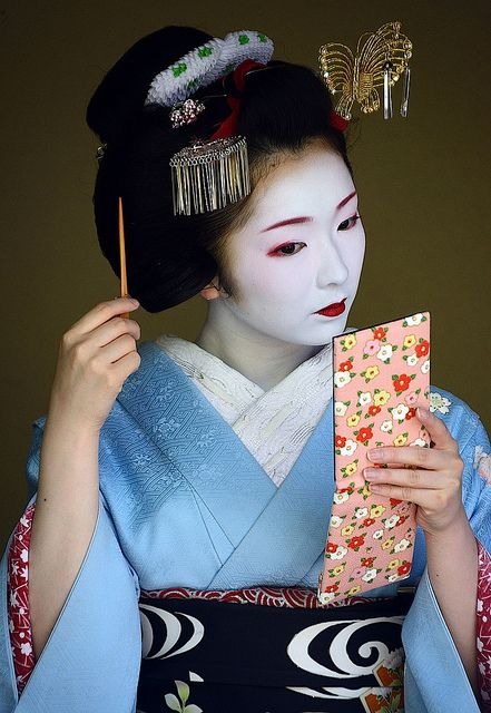 Toshimana fixing her hairstyle, Ofuku. She just recently became geiko.