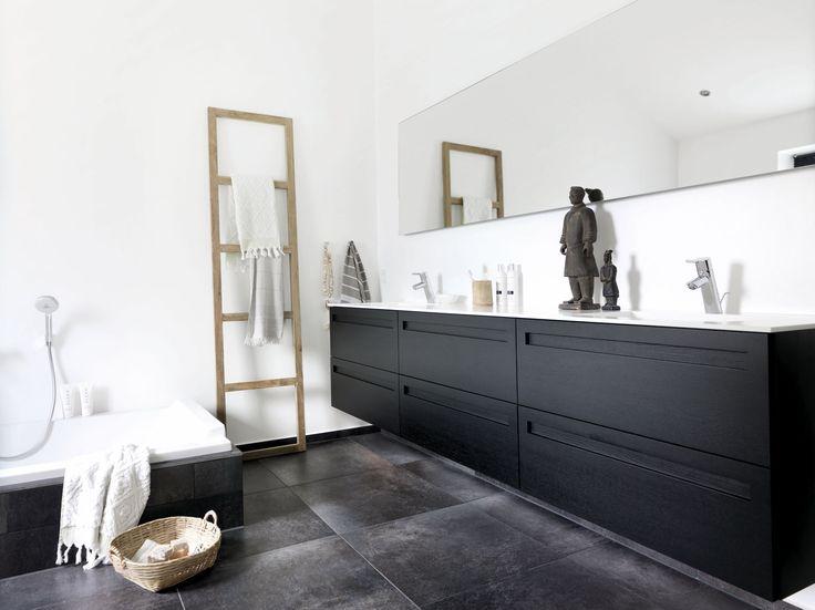 Maskulin luksus på badeværelset i Thyregod. Rummet domineres af store flader i sortbejdset eg med indfræsede greb, det lange spejl med indirekte belysning og nedsænket badekar. Se mere fra boligen på www.jke-design.dk.