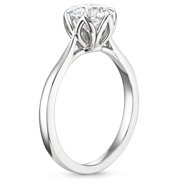 This simple claw prong solitaire features an open basket with six elegant leaves that cradle the center stone. The delicate band gently tapers at the top of the shoulders, bringing even more emphasis to the graceful setting.