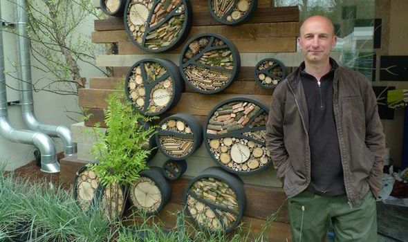 Nigel Dunnet by key features of his Gold medal winning RHS Chelsea show garden - insect houses attached to a wall of the bird hide on his roof garden design