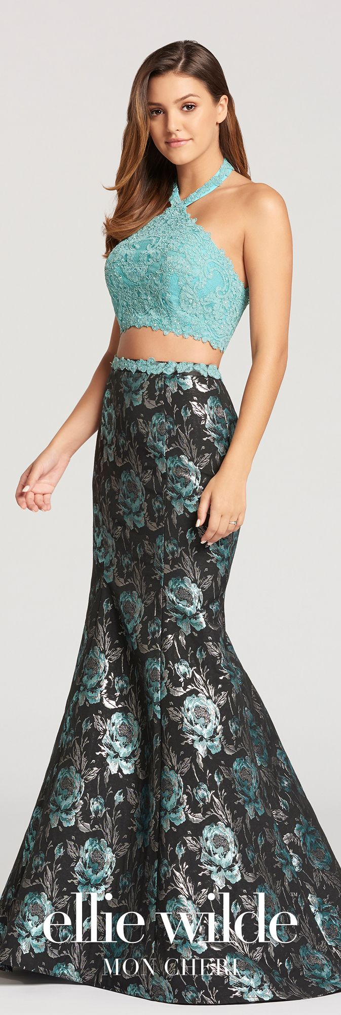 Two-piece sleeveless jacquard and lace trumpet dress with high V-halter neckline, a cropped lace scalloped bodice, and a high-waisted skirt.