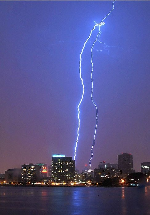 """Taken from Lake Merritt: A lightning bolt strikes over downtown Oakland on April 12, 2012. From Damon Tighe: """"Great storm over Oakland. Most of the bolts were at my back, but I was lucky to get one striking right where I was hoping it would: over downtown!"""" Photo: Damon Tighe / Courtesy photo"""